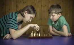 Niños hermosos que juegan a ajedrez Imagen de archivo