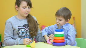 Niños hermosos que juegan con la pirámide plástica almacen de video