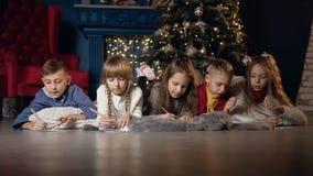 Niños hermosos que mienten en el piso mientras que drenaje algo en el papel metrajes