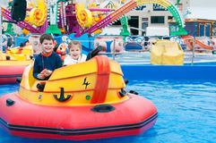 Niños hermosos que se divierten en un parque de atracciones Niños encendido imagenes de archivo