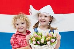 Niños holandeses con las flores del tulipán y la bandera holandesa Fotografía de archivo libre de regalías