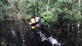 Niños indígenas en canoa en el río Amazonas almacen de video