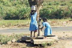 Niños indios en la bomba de agua Fotos de archivo