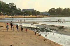 Niños indonesios y adultos que caminan en la playa fotos de archivo