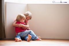 Niños infelices que se sientan en piso en esquina en casa fotos de archivo libres de regalías