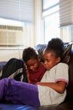 Niños infelices que se sientan en Sofa At Home imagen de archivo libre de regalías