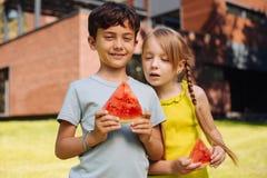 Niños inspirados que comen una sandía madura Fotos de archivo libres de regalías