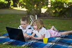 Niños jovenes con la computadora portátil Fotos de archivo libres de regalías