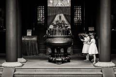 Niños jovenes de la generación que ruegan para la buena suerte en el templo chino fotos de archivo libres de regalías
