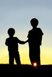 Niños jovenes de la silueta que llevan a cabo las manos en la puesta del sol Imágenes de archivo libres de regalías