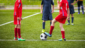 Niños jovenes de los muchachos en los uniformes que juegan a fútbol del fútbol de la juventud Imágenes de archivo libres de regalías