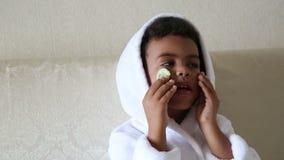 Niños jovenes en el salón de belleza con los pepinos en su cara almacen de video