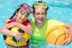 Niños jovenes felices en piscina Imagen de archivo libre de regalías