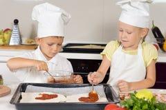 Niños jovenes que se hacen una pizza hecha en casa Fotos de archivo
