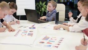 Niños jovenes que se sientan en los ordenadores portátiles en la oficina almacen de metraje de vídeo