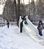 Niños, jugando en la colina de la nieve Imagenes de archivo