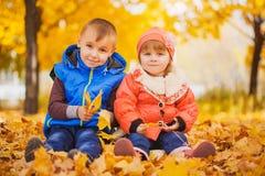 Niños juguetones felices en el parque del otoño imagen de archivo libre de regalías