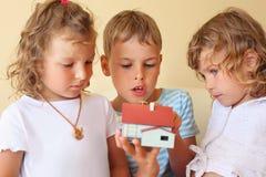 Niños junto que mantienen el modelo de las manos de la casa Fotos de archivo libres de regalías