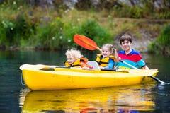 Niños kayaking en un río Imagen de archivo