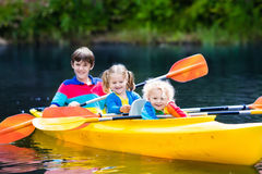 Niños kayaking en un río Foto de archivo libre de regalías