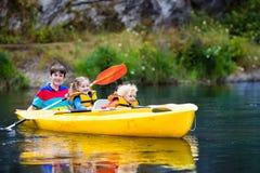 Niños kayaking en un río Fotografía de archivo