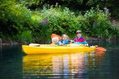Niños kayaking en un río Imágenes de archivo libres de regalías