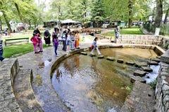 Niños a la edad de siete o de ocho que juegan en un parque de atracciones fotos de archivo