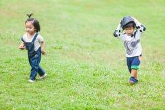 Niños lindos 2-3 años que corren en el jardín Imagen de archivo