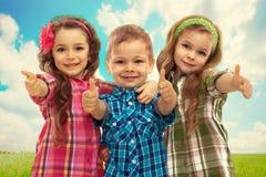 Niños lindos de la moda que muestran los pulgares para arriba Fotografía de archivo