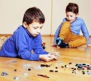 Niños lindos divertidos que juegan los juguetes en casa, sonrisa feliz de los muchachos, primera forma de vida del papel de la ed Imagen de archivo libre de regalías