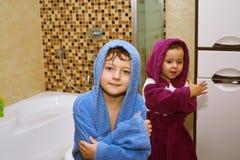 Niños lindos en albornoces en el cuarto de baño foto de archivo