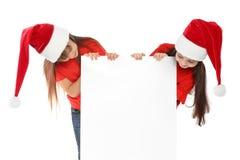 Niños lindos en los sombreros de Papá Noel con el cartel en blanco en el fondo blanco Celebración de la Navidad foto de archivo