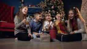 Niños lindos felices que se relajan en el piso y el té de consumición en el fondo del árbol de navidad metrajes