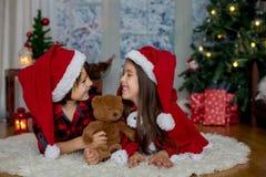 Niños lindos, muchacho y muchacha, divirtiéndose en la Navidad Imagenes de archivo