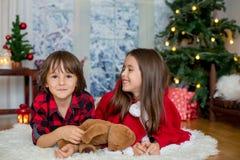 Niños lindos, muchacho y muchacha, divirtiéndose en la Navidad Foto de archivo libre de regalías