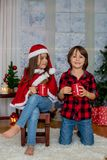 Niños lindos, muchacho y muchacha, divirtiéndose en la Navidad Imagen de archivo