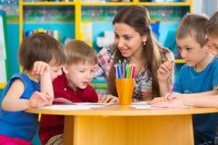 Niños lindos que dibujan con el profesor en la clase preescolar Foto de archivo libre de regalías