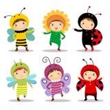Niños lindos que llevan los trajes del insecto y de la flor