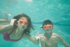 Niños lindos que presentan bajo el agua en piscina Imagenes de archivo