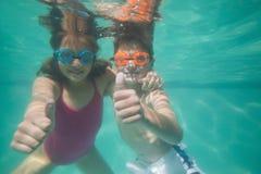 Niños lindos que presentan bajo el agua en piscina Fotografía de archivo