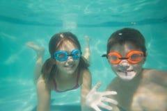 Niños lindos que presentan bajo el agua en piscina Fotos de archivo libres de regalías