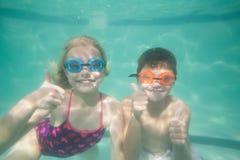 Niños lindos que presentan bajo el agua en piscina Foto de archivo libre de regalías