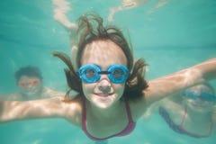 Niños lindos que presentan bajo el agua en piscina Imagen de archivo