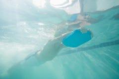 Niños lindos que presentan bajo el agua en piscina Foto de archivo