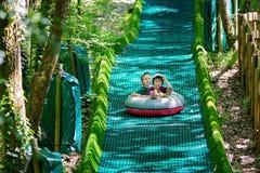 Niños lindos, yendo abajo en una diapositiva grande en un trineo del verano del círculo Imagen de archivo libre de regalías