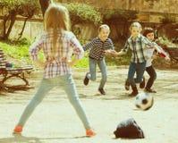 Niños menores que juegan a fútbol de la calle al aire libre Foto de archivo libre de regalías