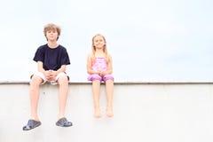 Niños - muchacha y muchacho que se sientan en el tejado Imagen de archivo libre de regalías