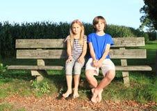 Niños - muchacha y muchacho que se sientan en un banco imágenes de archivo libres de regalías