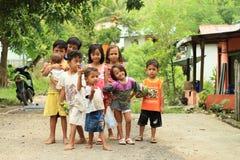 Niños - muchachas que presentan en la calle de Labuan Bajo Fotos de archivo