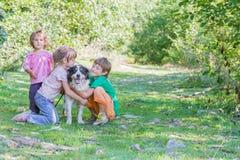 Niños - muchacho y muchacha - con el perro al aire libre Fotos de archivo libres de regalías